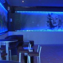Decoración de local de copas con arte y atrezzo. Rollo de película realizado en carpintería con iluminación y graffiti de fondo.