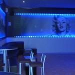 Decoración de local de copas con arte y atrezzo. Iluminación y graffiti que imitando un rollo de película realizado en carpintería.