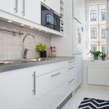 Cocina con encimera en aluminio y muebles a medida blancos con tiradores en aluminio.