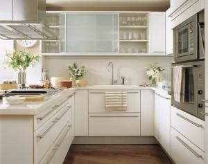 Cocina a medida en U con zonas de uso separadas en color claro.